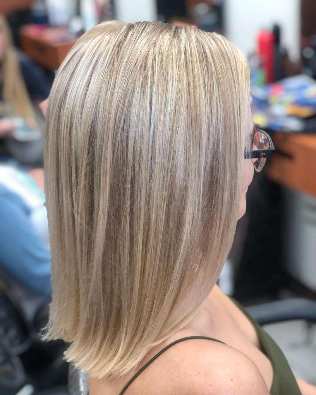 Proste i zaczesane na bok cięcie w kolorze blond